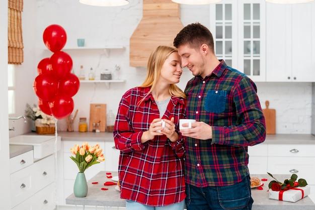 Casal de tiro médio com copos de café dentro de casa