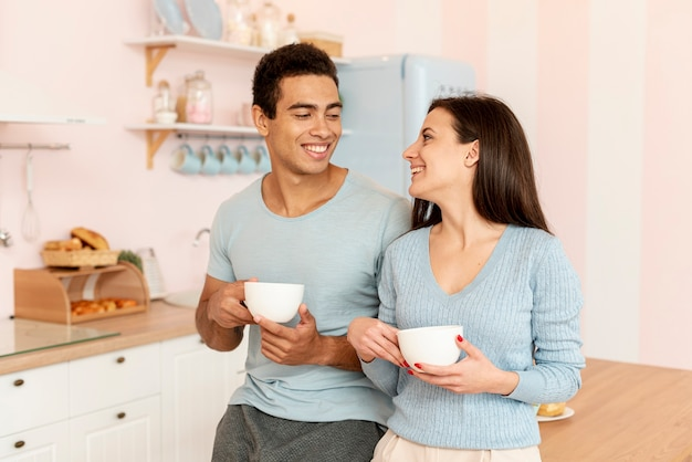 Casal de tiro médio com copos de café na cozinha