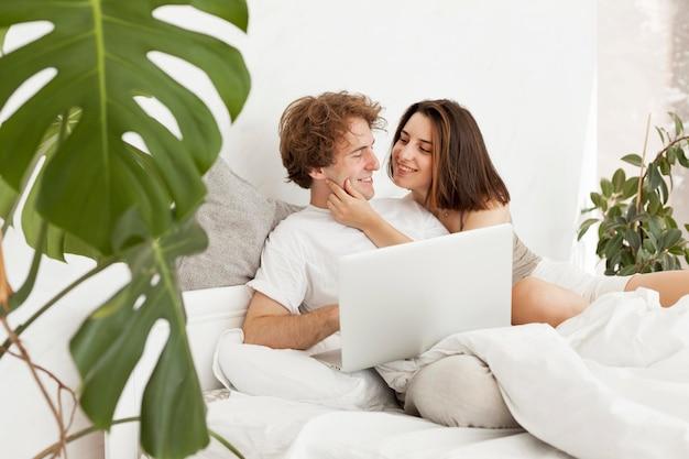 Casal de tiro médio com laptop na cama