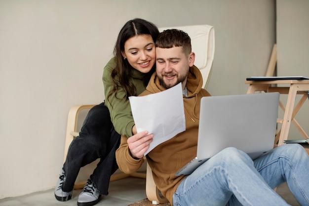 Casal de tiro médio com laptop