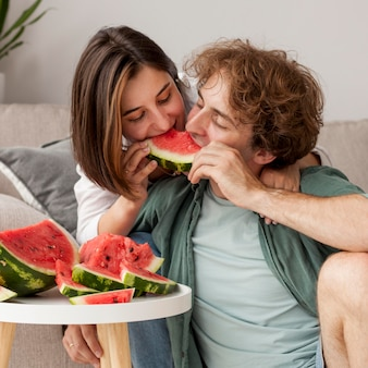 Casal de tiro médio comendo melancia
