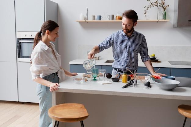 Casal de tiro médio cozinhando juntos