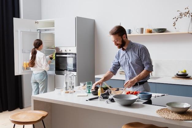 Casal de tiro médio cozinhando na cozinha