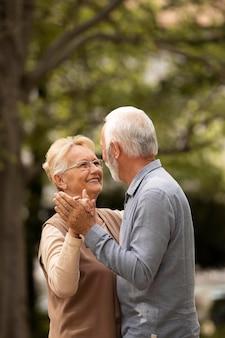 Casal de tiro médio dançando ao ar livre