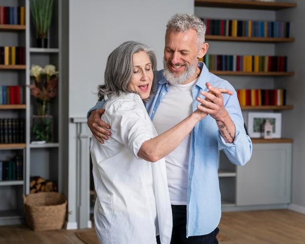 Casal de tiro médio dançando em casa