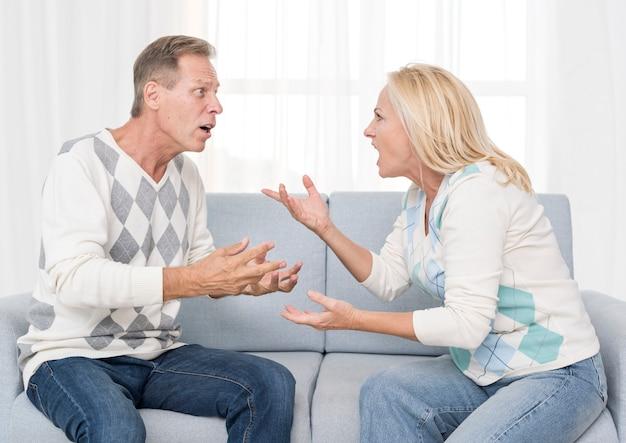 Casal de tiro médio discutindo no sofá