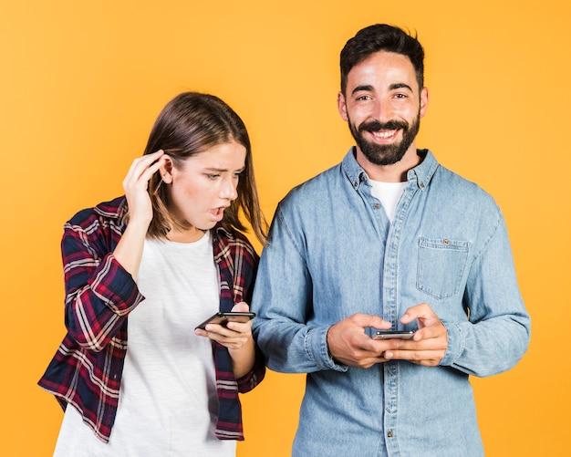 Casal de tiro médio em seus telefones