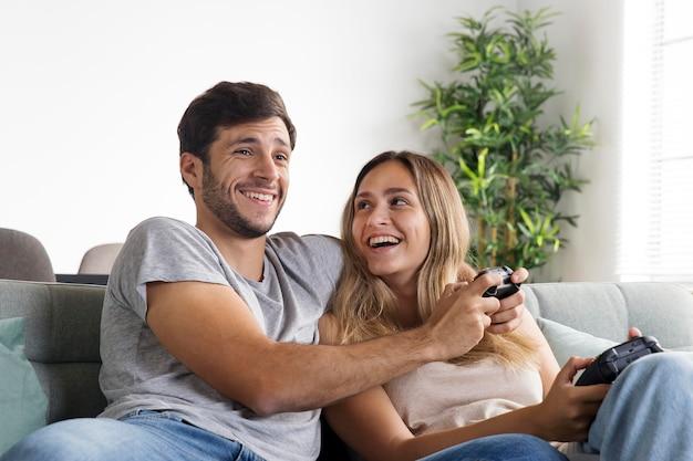 Casal de tiro médio jogando no sofá