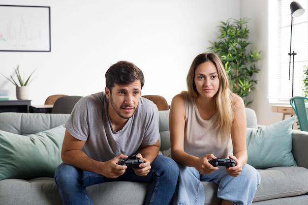 Casal de tiro médio jogando videogame