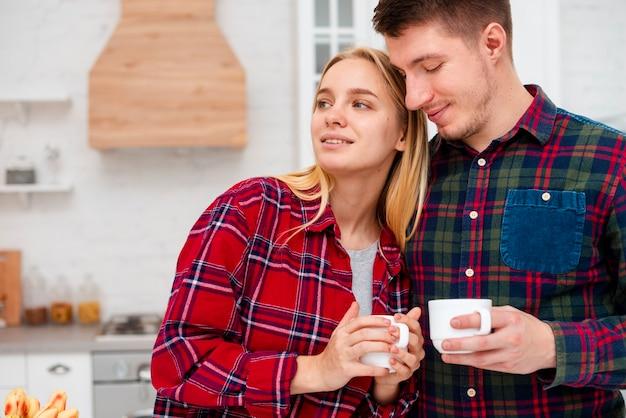 Casal de tiro médio na cozinha com copos de café