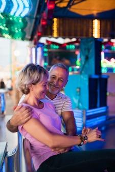 Casal de tiro médio no parque de diversões sentado