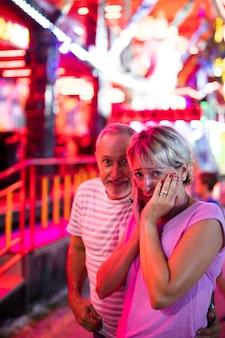 Casal de tiro médio no parque de diversões