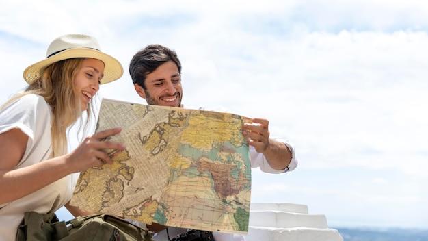 Casal de tiro médio olhando para o mapa