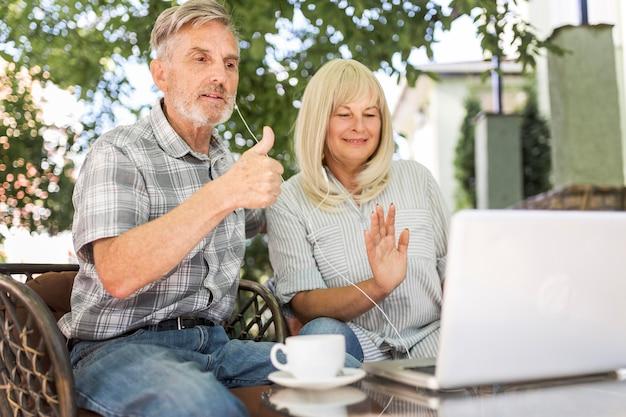 Casal de tiro médio olhando para um laptop
