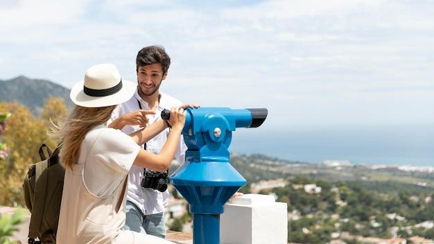 Casal de tiro médio perto do telescópio