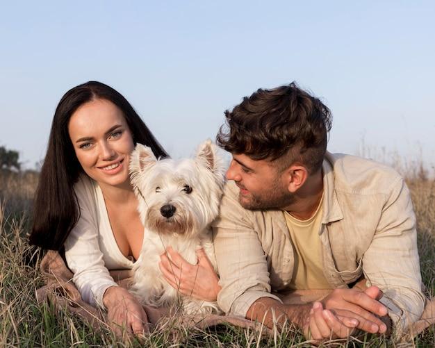 Casal de tiro médio posando com cachorro
