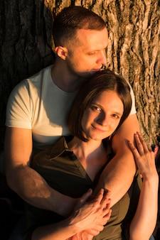 Casal de tiro médio posando perto de uma árvore