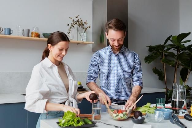 Casal de tiro médio preparando comida na cozinha