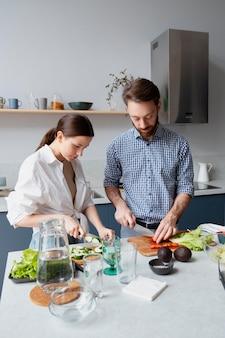 Casal de tiro médio preparando comida saudável
