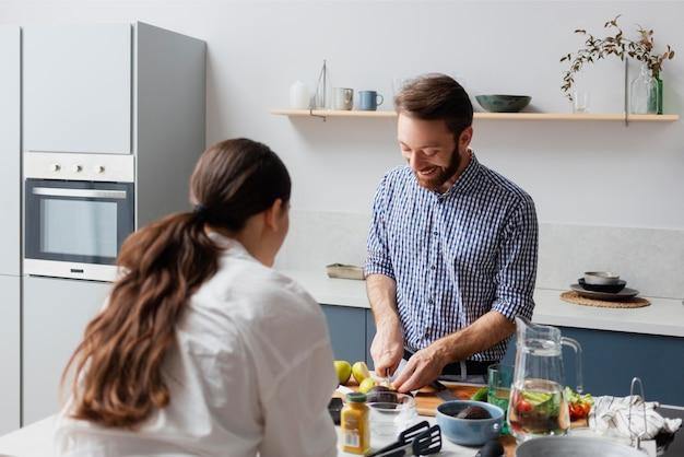 Casal de tiro médio preparando comida