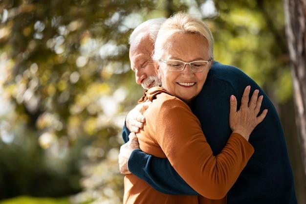 Casal de tiro médio se abraçando do lado de fora