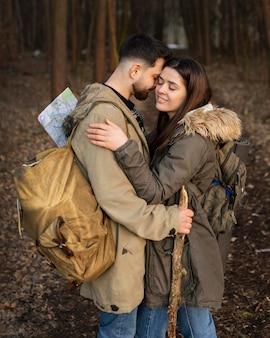 Casal de tiro médio se abraçando na floresta