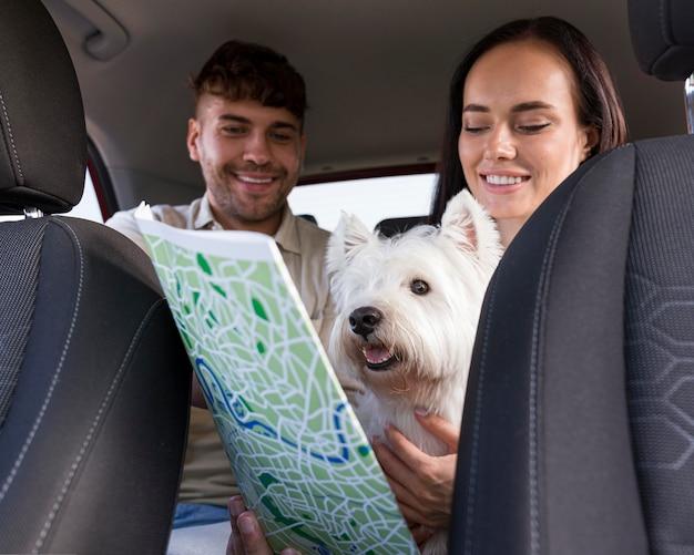 Casal de tiro médio segurando cachorro e mapa