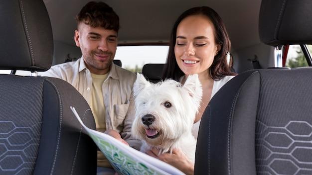 Casal de tiro médio segurando mapa e cachorro
