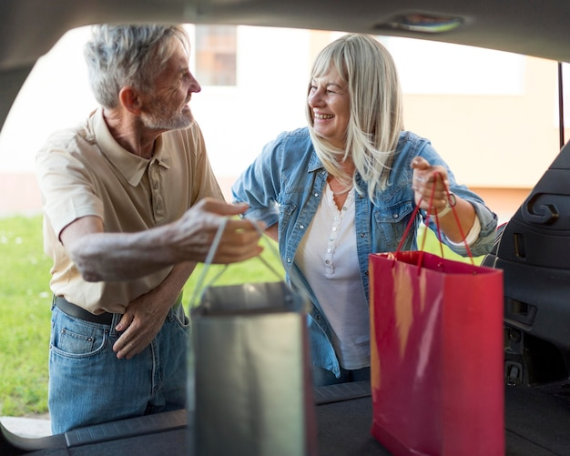 Casal de tiro médio segurando sacolas de compras