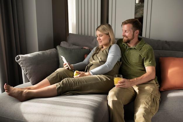 Casal de tiro médio sentado no sofá