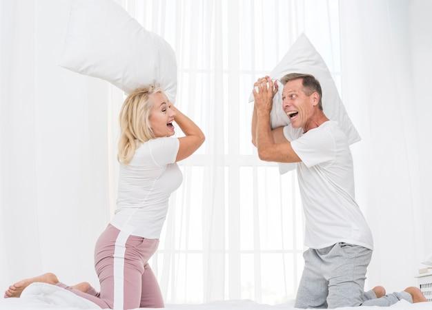 Casal de tiro médio tendo uma luta de almofadas