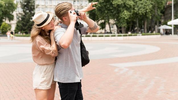 Casal de tiro médio tirando fotos