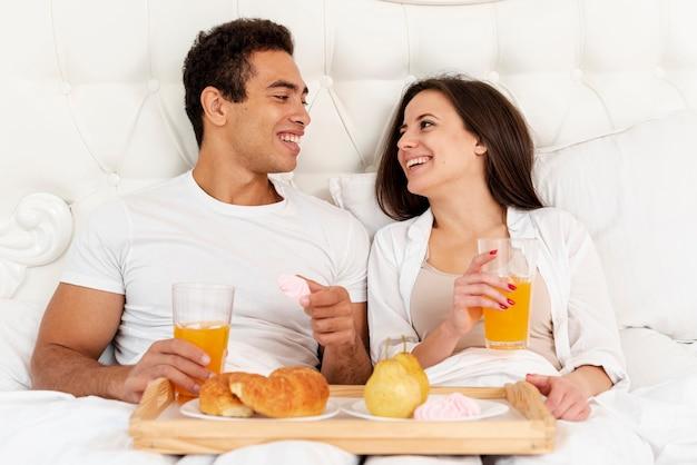 Casal de tiro médio tomando café da manhã na cama