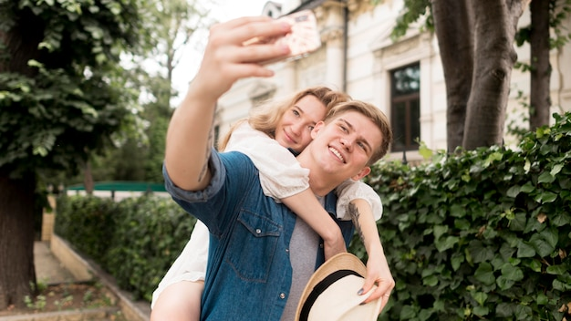 Casal de tiro médio tomando selfie