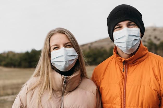 Casal de tiro médio usando máscaras médicas