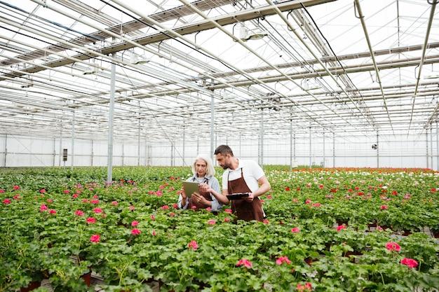 Casal de trabalhadores em pé no jardim perto de flores e falando