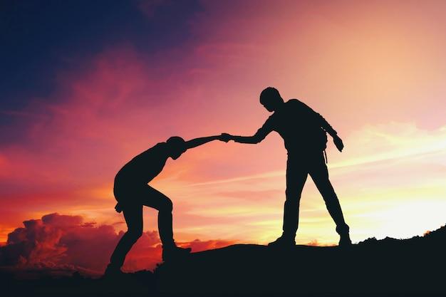 Casal de trabalho em equipe, ajudando a caminhar uns aos outros a silhueta nas montanhas