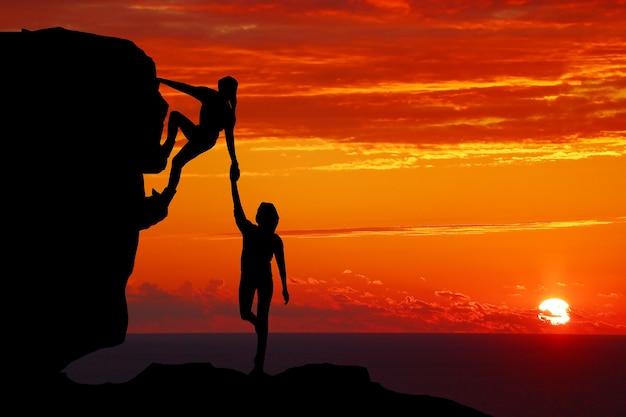 Casal de trabalho em equipe, caminhadas ajuda um ao outro a confiar na silhueta de assistência nas montanhas, por do sol. trabalho em equipe de alpinista homem e mulher, ajudando um ao outro no topo da equipe de alpinismo