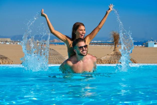 Casal de turista às costas na piscina de borda infinita