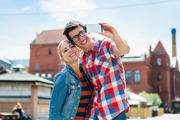 Casal de turista levando selfie no telhado em berlim