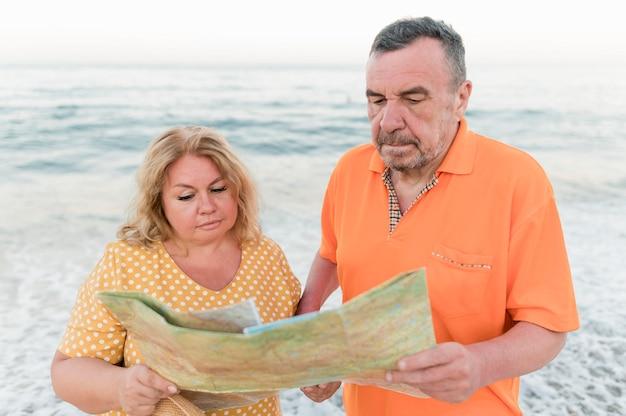 Casal de turista mais velho na praia com mapa