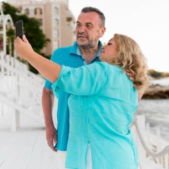 Casal de turista mais velho tomando uma selfie na praia