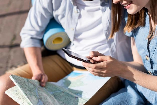 Casal de turista olhando para o telefone e o mapa