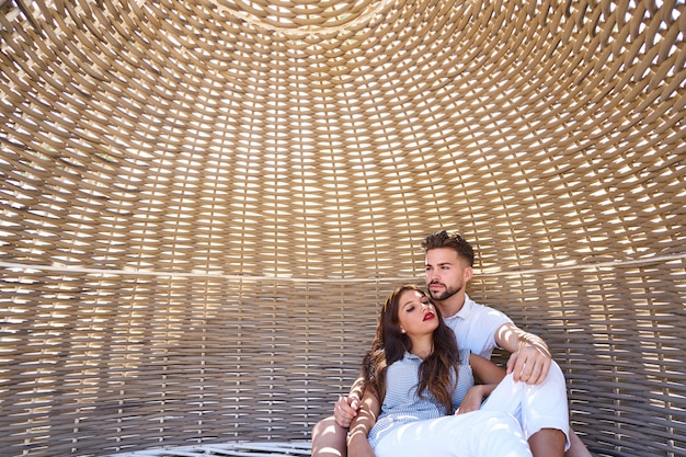 Casal de turista relaxado dentro de um guarda-sol de praia