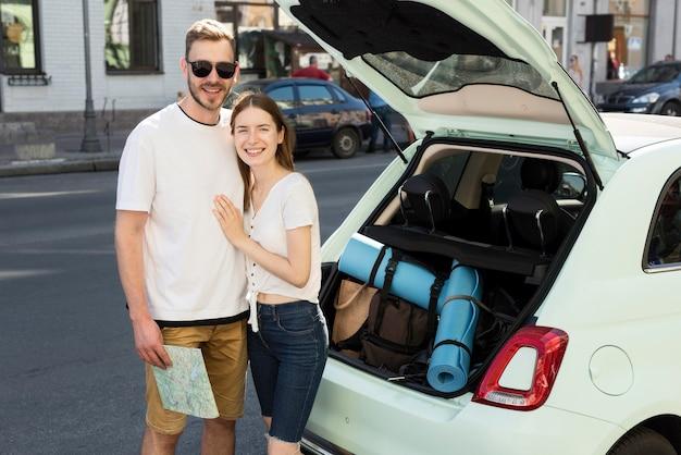Casal de turista se preparando para sair para viagem com carro