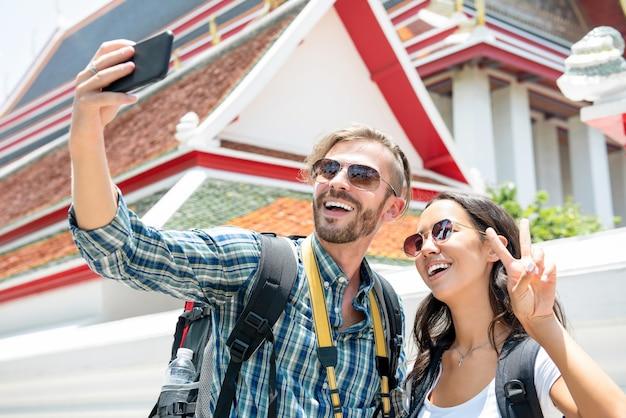 Casal de turista tomando selfie no templo tailandês de férias na tailândia