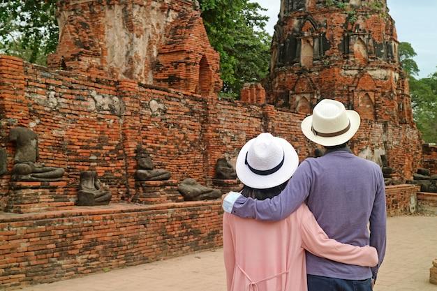 Casal de turistas admirando um grupo de imagens de buda sem cabeça no parque histórico de ayutthaya, tailândia