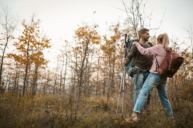 Casal de turistas apaixonados fica abraçando, apoiando-se em bastões para caminhadas. jovem homem caucasiano e mulher no fundo de uma jovem floresta de outono. conceito de suporte
