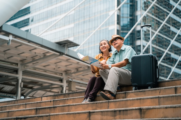 Casal de turistas asiáticos idosos visitando a capital alegremente e se divertindo e olhando o mapa para encontrar lugares para visitar.