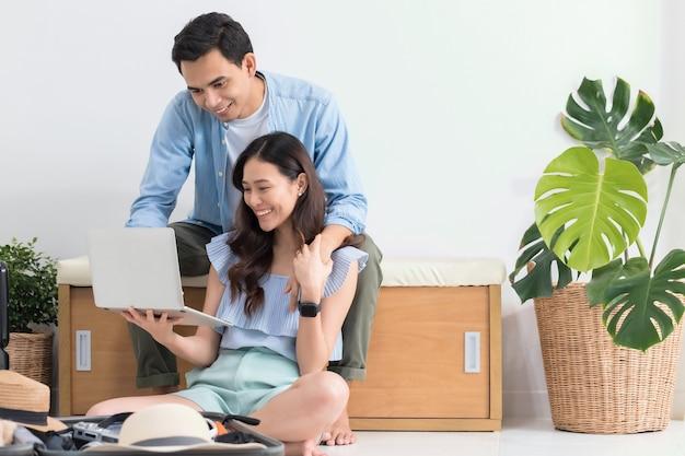 Casal de turistas asiáticos planejando informações de viagem com laptop e fazendo malas para viajar antes da data de viagem em casa, segundo plano.